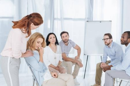 psychotherapist supporting middle aged woman during group therapy
