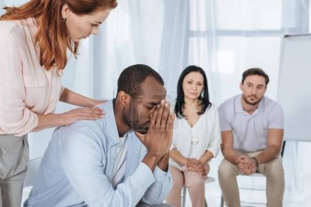 middle aged people supporting upset african american man during anonymous group therapy