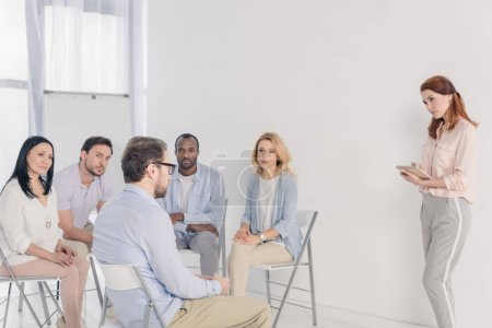 psychotherapist taking notes and working with multiethnic people sitting on chairs during group therapy