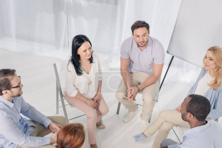 high angle view of smiling multiethnic middle aged people sitting on chairs and talking during group therapy