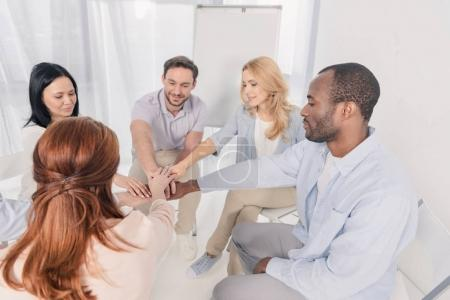 smiling middle aged multiethnic people stacking hands during group therapy