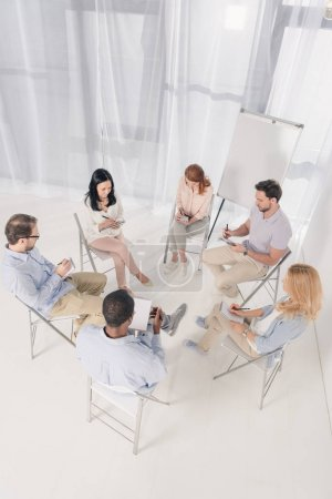 overhead view of multiethnic middle aged people taking notes in notebooks during group therapy