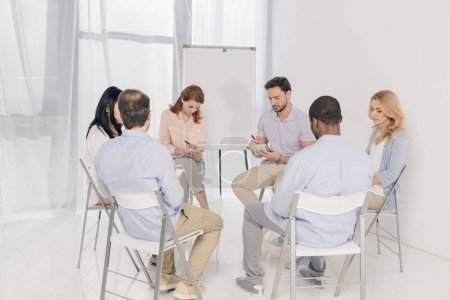multiethnic middle aged people taking notes in notebooks during group therapy