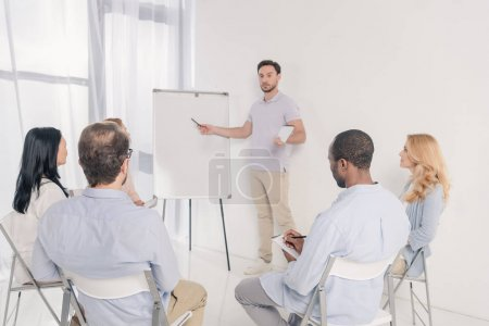 male psychotherapist pointing at blank whiteboard and multiethnic group of people sitting on chairs during therapy