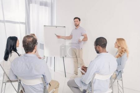 Photo pour Psychothérapeute masculin pointant vers le tableau blanc vierge et le groupe multiethnique de personnes assises sur des chaises pendant la thérapie - image libre de droit