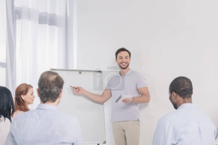 smiling man holding notebook and pointing at blank whiteboard while looking at multiethnic people during group therapy