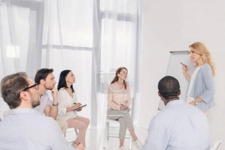psychothérapeute femelle pointant sur tableau blanc blanc et groupe multiethnique, assis sur des chaises au cours du traitement