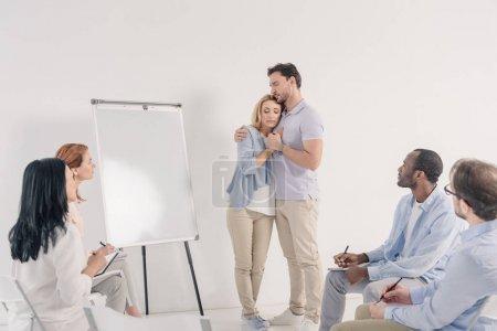 Photo pour Couple d'âge moyen tenant la main tout en se tenant près du tableau blanc vierge et d'autres personnes assises sur des chaises pendant la thérapie de groupe - image libre de droit