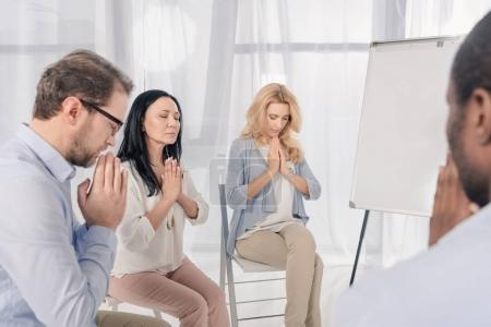 Foto de Recortada la foto de grupo anónimo de personas multiétnicas orando durante la terapia - Imagen libre de derechos