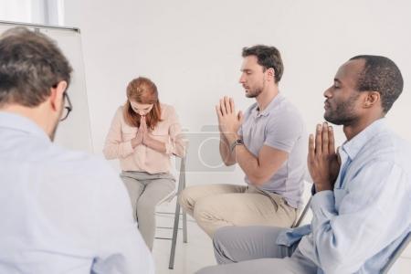 Foto de Recortada de tiro del grupo anonymous orando durante la terapia - Imagen libre de derechos