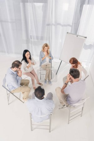 overhead view of middle aged multiethnic people praying at group therapy