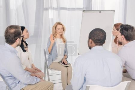 Photo for Middle aged woman holding hand on Holy Bible while sitting with multiethnic people on chairs at group therapy - Royalty Free Image