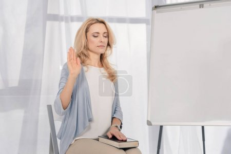 mature woman with closed eyes and hand in Holy Bible sitting on chair indoors
