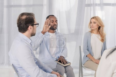 african american man with closed eyes holding hand on Holy Bible during anonymous group therapy