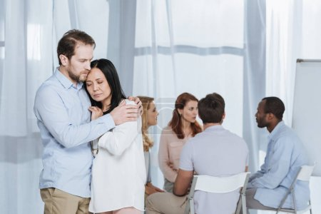 upset mature couple hugging while people sitting on chairs behind during group therapy