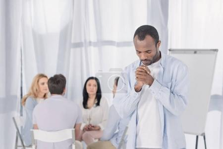 african american praying while people sitting behind during group therapy