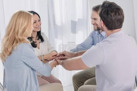 middle aged people sitting and stacking hands during group therapy
