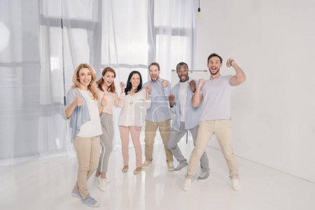 Photo for Happy multiethnic mid adult people triumphing and smiling at camera - Royalty Free Image