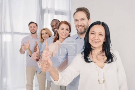 middle aged people smiling at camera and showing thumbs up during group therapy
