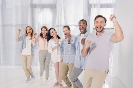Foto de Gente envejecida media multiétnica sonriendo a cámara y triunfando durante la terapia de grupo - Imagen libre de derechos