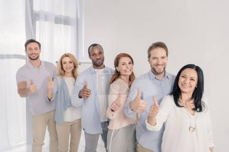multiethnic middle aged people smiling at camera and showing thumbs up during group therapy