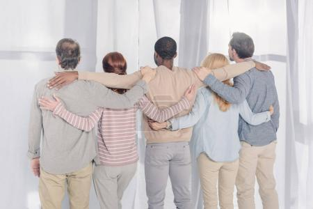 rear view of multiethnic people standing and embracing during group therapy