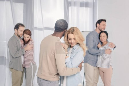 three multiethnic couples hugging during psychotherapy