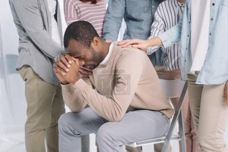 cropped shot of people supporting depressed middle aged african american man during group therapy
