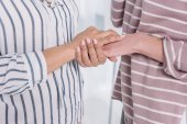 cropped shot of two people holding hands and supporting each other