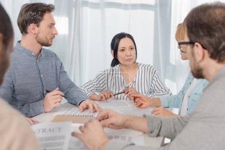 Photo pour Âge moyen multiethnique personnes signature du contrat à une thérapie de groupe anonyme - image libre de droit