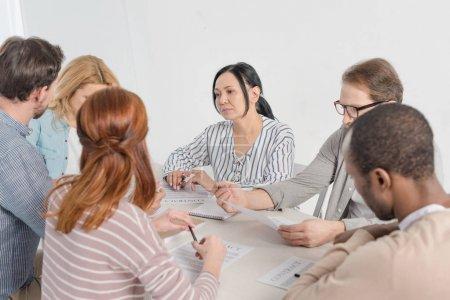 Photo pour Groupe multi-ethnique de personnes travaillant de concert avec papiers - image libre de droit