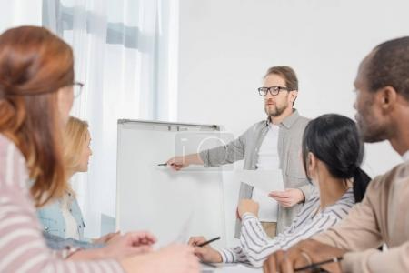 male psychoanalyst pointing at whiteboard white people gathered around table at anonymous group therapy