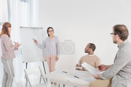 multiethnic women with pens standing near blank whiteboard and middle aged men sitting on foreground