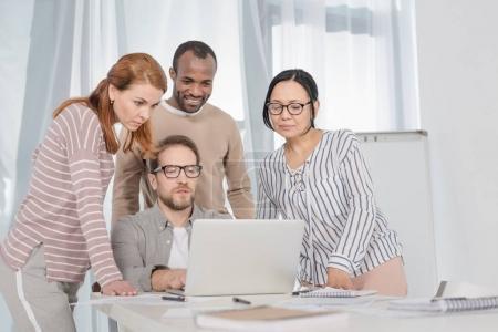 Foto de Grupo multiétnico de medio de personas que utilizan ordenador portátil juntos - Imagen libre de derechos