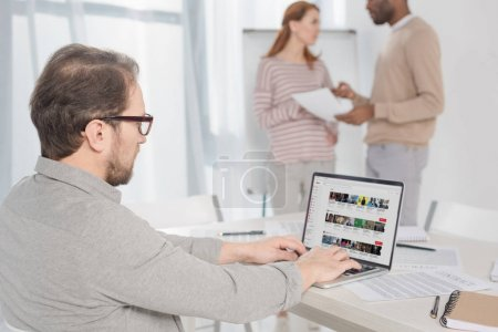 middle aged man in in eyeglasses using laptop with youtube website on screen in office