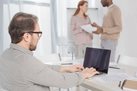 middle aged man in in eyeglasses using laptop with blank screen in office