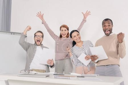 Foto de Gente envejecida media multiétnica emocionada sujetando papeles y triunfando - Imagen libre de derechos