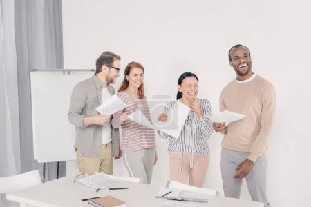 Photo for Happy multiethnic middle aged people holding papers and laughing - Royalty Free Image
