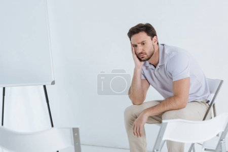 Photo for Depressed man sitting and looking away in empty room - Royalty Free Image
