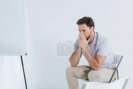 depressed man sitting and looking away indoors