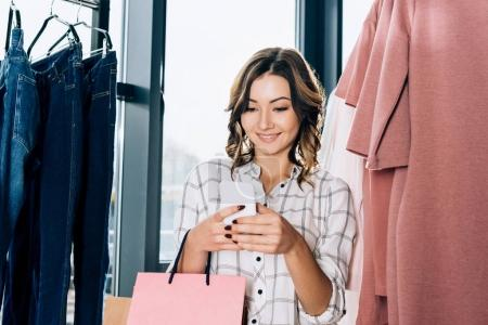 smiling young woman using smartphone on shopping