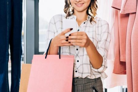 cropped shot of stylish woman using smartphone on shopping