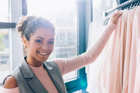 smiling young woman choosing new clothes in store