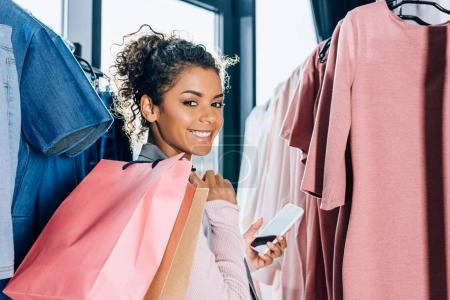 beautiful young woman with smartphone and shopping bags in clothing store