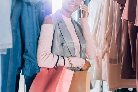 cropped shot of woman talking by phone while spending time in clothes store