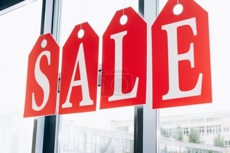 sale sign made of tags with letters on windows of boutique