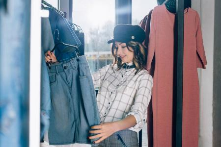 beautiful young woman looking for new clothes in store