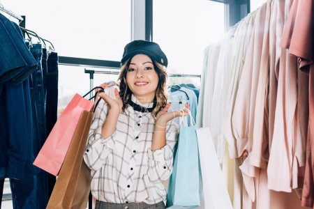 happy beautiful woman with shopping bags in clothing store