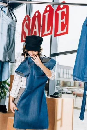 happy young woman looking at blue denim dress at clothing store