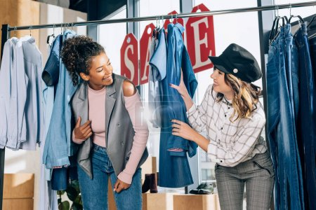 young stylish shopping buddies having fun in clothing store